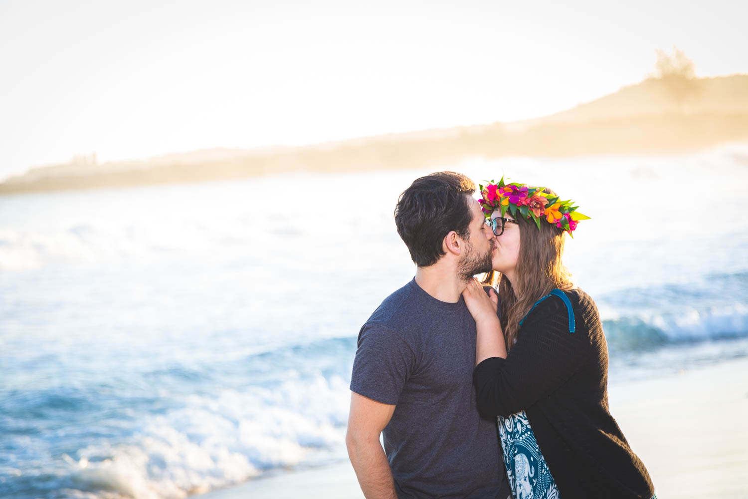 Adorable couple kissing during a Maui portrait photography session at the beach at sunrise.