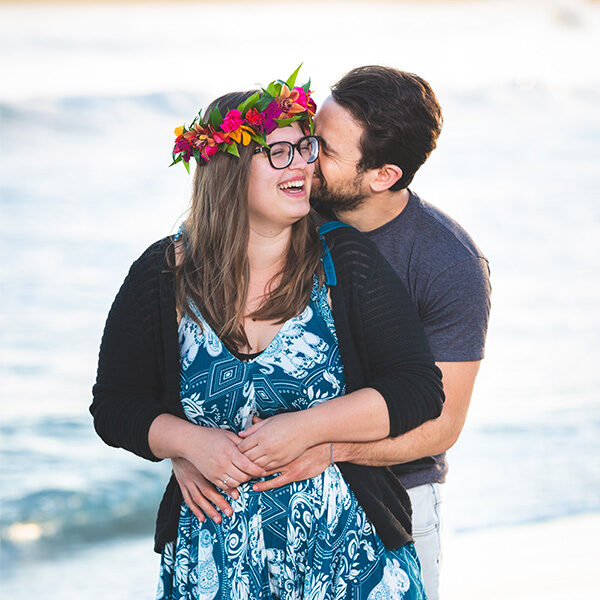 Happy couple dressed in blues and greens with a flower head lei are holding each other laughing at the beach during this sunrise Maui couple photography session.