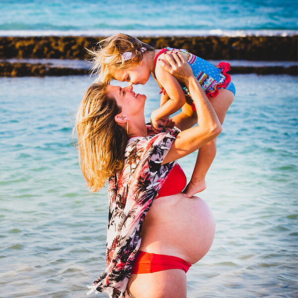 Pregnant mom in red bathing suit holds her cute daughter in the sky as they touch nose to nose at the beach during this Maui family photography session.