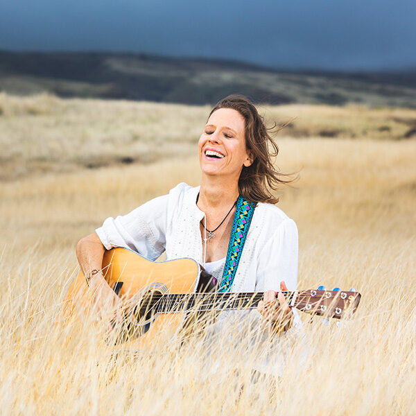 Maui portrait photography session of a beautiful woman in white blouse plays guitar and sings in golden grass with a rich dark blue sky in the background.