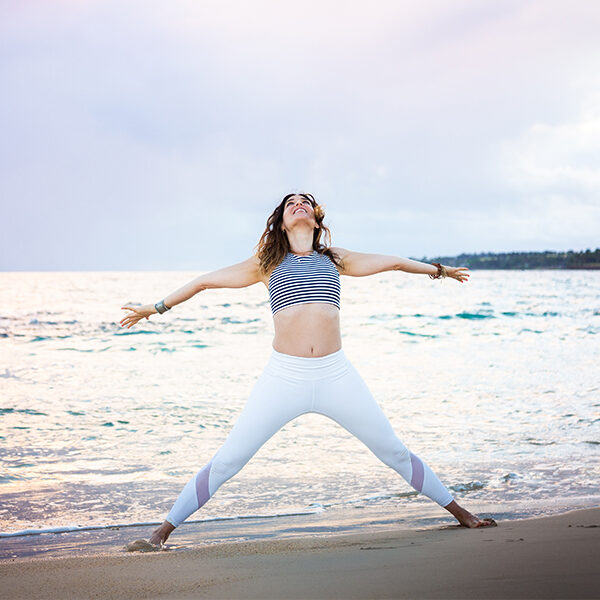 Beautiful woman in white leggings and stripe shirt stands in a power pose with open arms rising to the sky as the sun is rising in the background at this epic Maui beach.